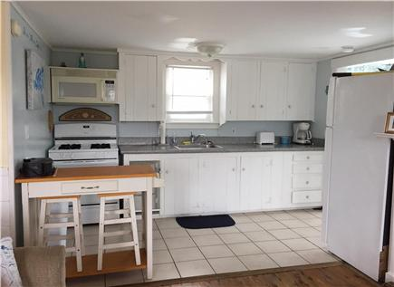 West Dennis Cape Cod vacation rental - Galley style kitchen with table and stools