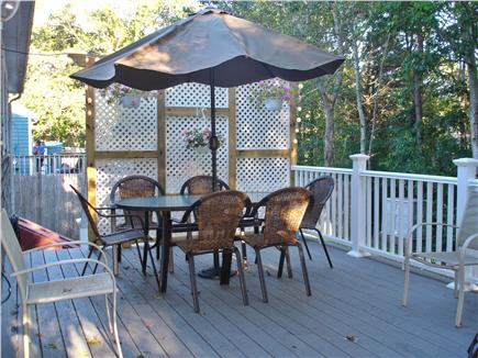 West Yarmouth Cape Cod vacation rental - Deck with patio set overlooking wooded yard