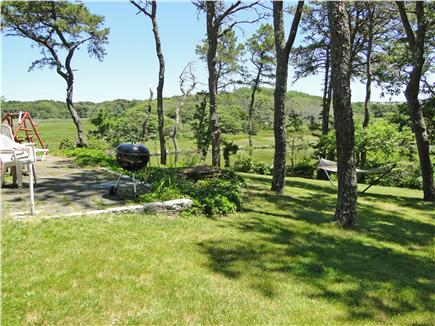 South Chatham Cape Cod vacation rental - Back yard area faces water with grill, lounging chairs, hammock.