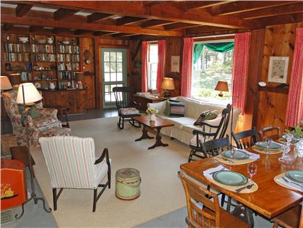 East Orleans Cape Cod vacation rental - Living room with woodwork, windows facing the water, door to deck