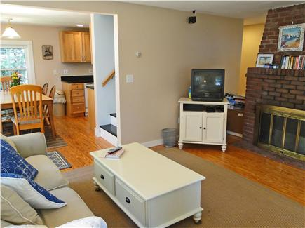 South Dennis Cape Cod vacation rental - Living room includes fireplace and TV, opens to dining area