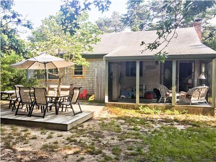 Eastham Cape Cod vacation rental - Backyard view with large deck and screened porch