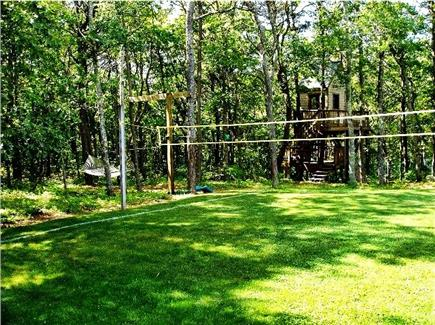 Pocasset Pocasset vacation rental - Volleyball area in side yard with treehouse in background