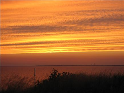 Truro - Corn Hill Cape Cod vacation rental - Northbound View: A sunset over PTown from cottage porch